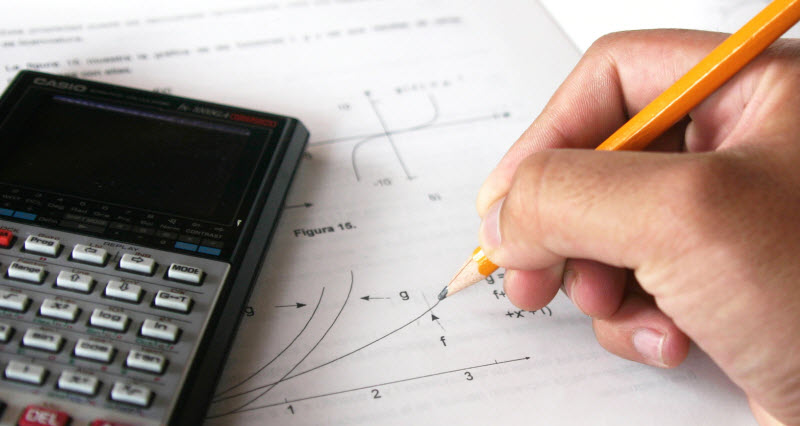 View of a hand solving a math equation with calculator beside