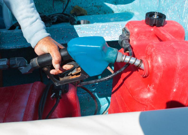 Man fueling red plastic tank