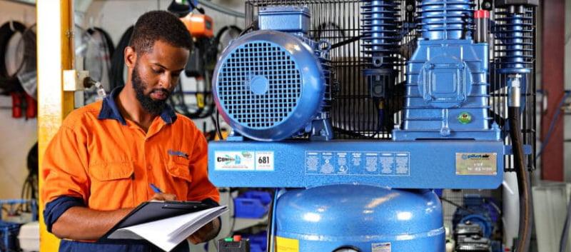 Man wearing orange shirt checking the air compressor