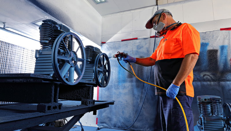 Man painting the machine of the compressor