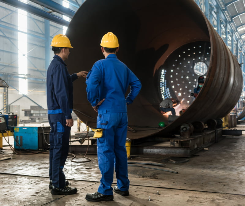 Two experienced workers supervising the manufacture of a metallic cylinder