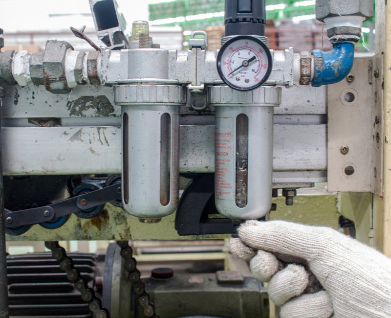 worker checking the air filter regulator pneumatic system factory
